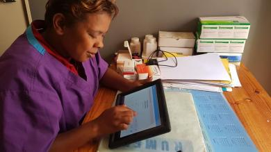 A midwife in a health center in Antananarivo checks data of women she has treated during the day. Pregnant women can pay using mTOMADY at this health center.